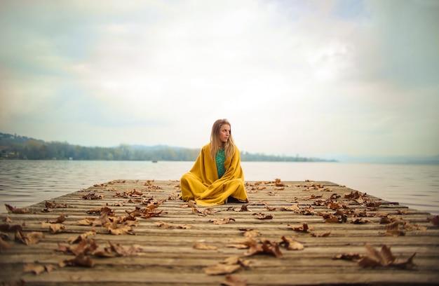Mädchen, das auf einem pier, den horizont schauend sitzt