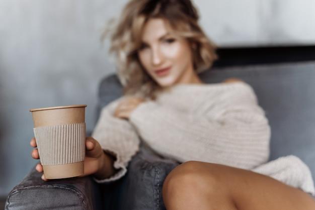 Mädchen, das auf einem sofa hält ein glas kaffee auf einem ausgestreckten arm sitzt. konzentrieren sie sich auf ein glas kaffee
