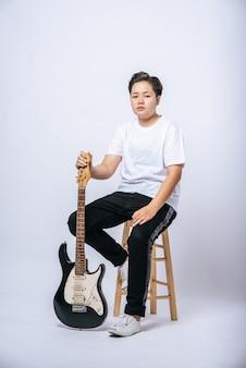 Mädchen, das auf einem stuhl sitzt und eine gitarre hält.
