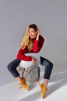 Mädchen, das auf einem stuhl sitzt und einen grauen rucksack hält