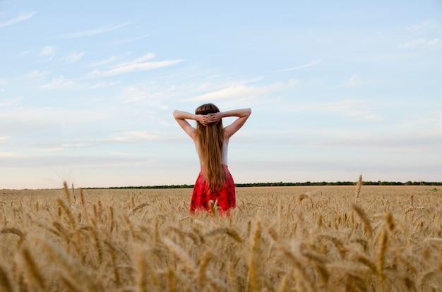Mädchen, das auf einem weizengebiet mit seinen händen hinter seinem kopf, der nächtliche himmel gesehen von hinten steht
