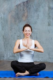 Mädchen, das auf einer blauen yogamatte im lotussitz sitzt und meditiert.