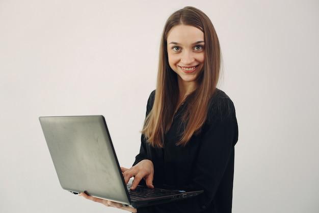 Mädchen, das auf einer weißen wand mit einem laptop steht