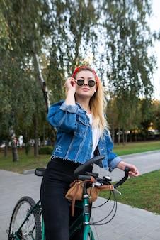 Mädchen, das auf fahrt in einem fahrradpark steht und brille repariert