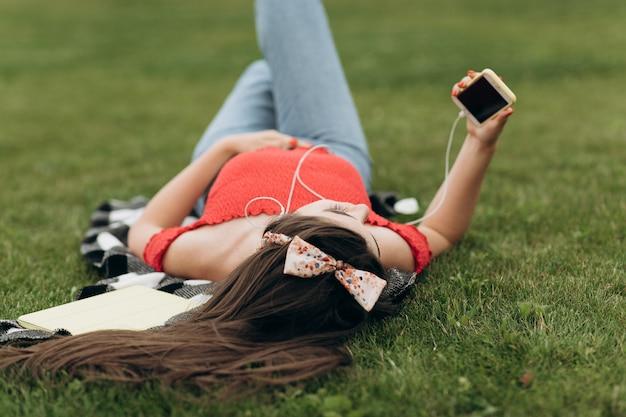 Mädchen, das auf gras stillsteht und musik hört