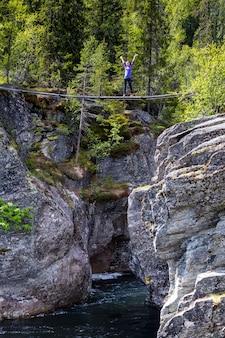 Mädchen, das auf hängebrücke steht. canyon view bei tre weltberühmten wasserfall rjukandefossen, norwegen