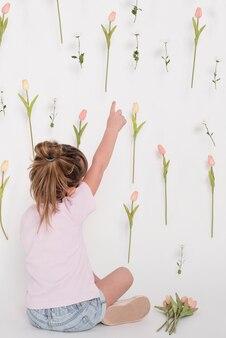 Mädchen, das auf hintere ansicht der tulpe zeigt