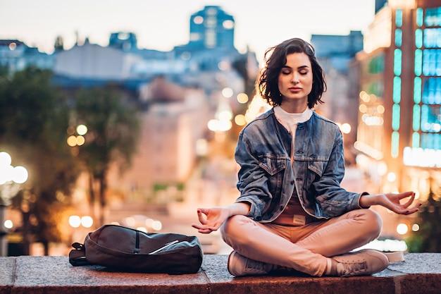 Mädchen, das auf hintergrund der abendstadt meditiert