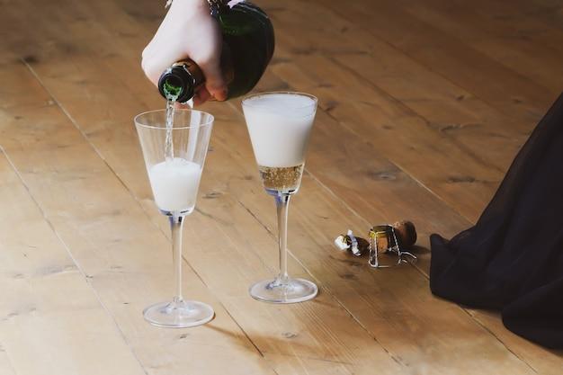 Mädchen, das auf holzboden sitzt, der champagner in zwei gläsern gießt. feier in informeller umgebung.