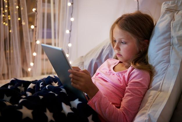 Mädchen, das auf ihrem bett liegt, während sie ein digitales tablett benutzt