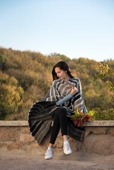 Mädchen, das auf naturhintergrund in der decke des herbstlaubs in ihren händen sitzt. vertikaler rahmen.