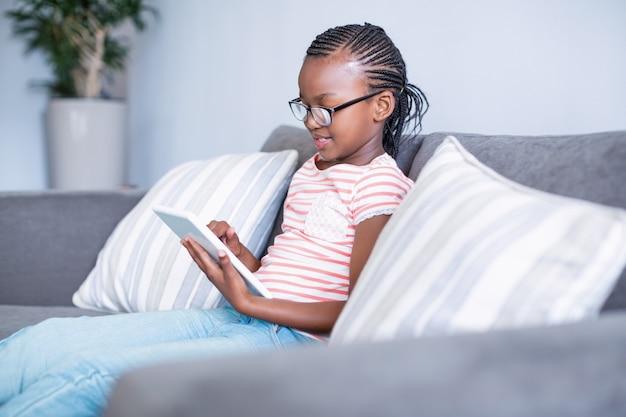Mädchen, das auf sofa mit digitalem tablett sitzt