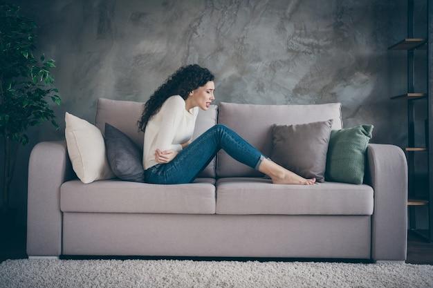 Mädchen, das auf sofa sitzt, das unter medizinischem bauchproblem im innenraum-wohnzimmer des modernen loft-industriestils leidet