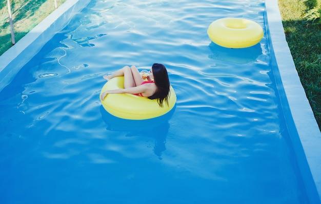Mädchen, das auf strandmatratze schwimmt