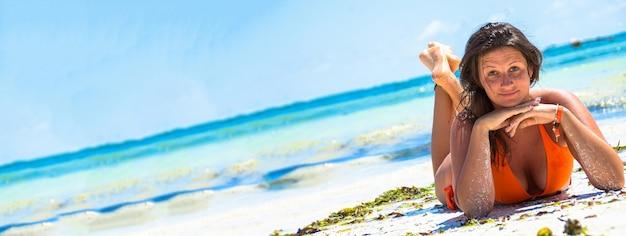 Mädchen, das auf strandurlaub liegt, fahnenbild mit kopienraum