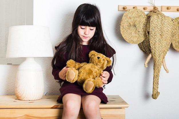 Mädchen, das auf tabelle mit weichem spielzeug sitzt
