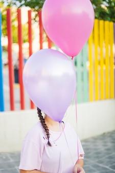 Mädchen, das ballone hält