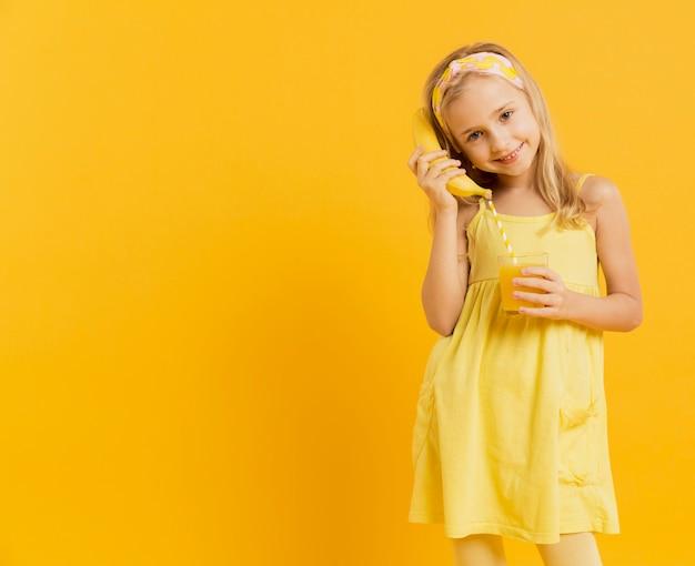 Mädchen, das banane als telefon mit kopienraum verwendet
