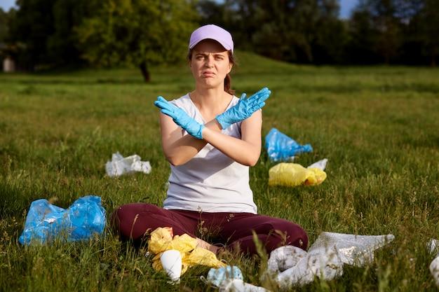 Mädchen, das baseballmütze und freizeithemd trägt, auf grünem gras sitzt und hände kreuzt, fordert, den planeten nicht zu verschmutzen, umgeben von müll, verärgert zu sein, ökologische probleme zu lösen.