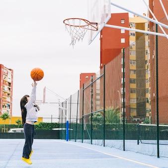 Mädchen, das basketball auf sportplatz spielt