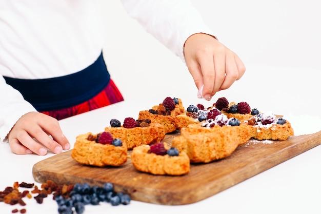 Mädchen, das beerenkuchen mit zuckerpulver verziert