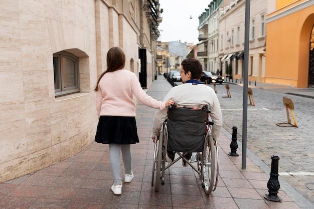 Mädchen, das behinderten männern hilft, in der stadt zu reisen