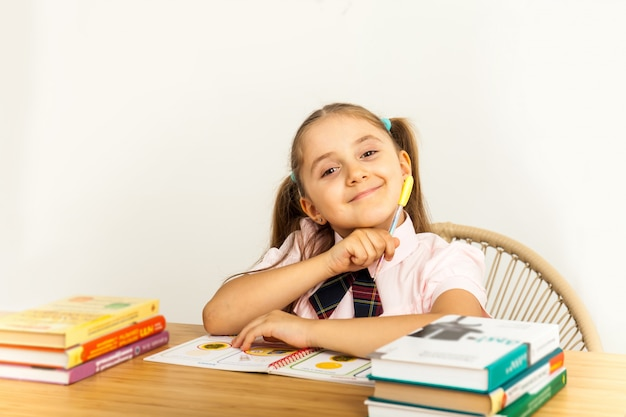Mädchen, das bei tisch auf weißem hintergrund studing ist