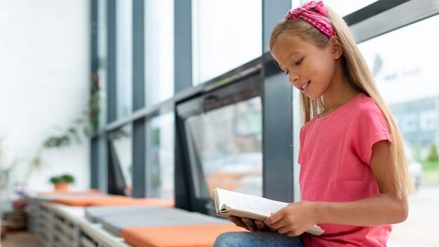 Mädchen, das beim sitzen neben dem fenster mit kopierraum liest