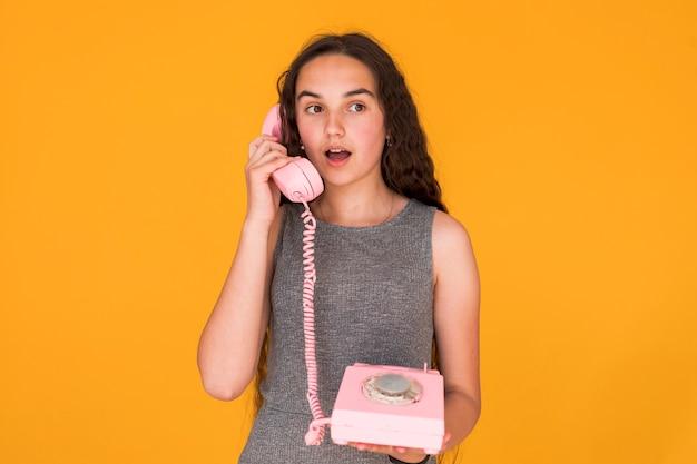 Mädchen, das beim sprechen am telefon entsetzt schaut