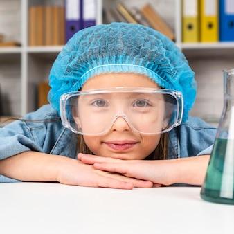 Mädchen, das beim tragen des haarnetzes und der schutzbrille für wissenschaftliche experimente aufwirft