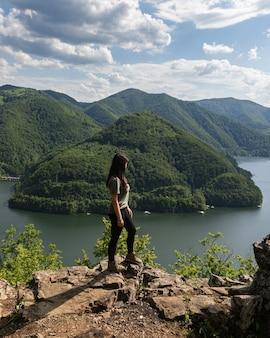Mädchen, das bergseelandschaft in tarnita, siebenbürgen, rumänien übersieht
