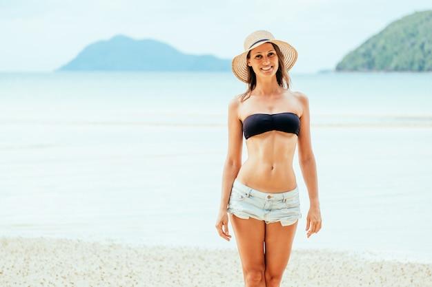 Mädchen, das bikini und hut am sandstrand trägt