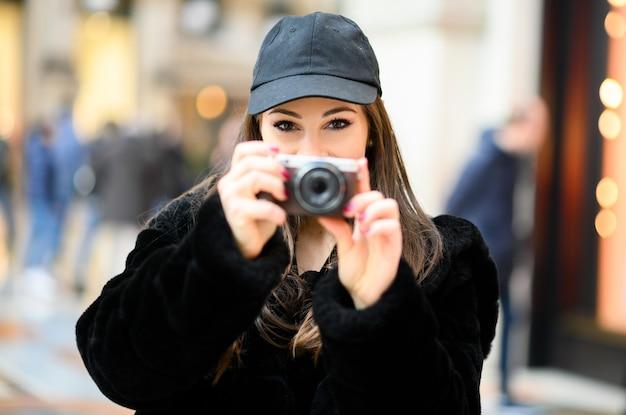 Mädchen, das bilder mit einer digitalkamera im freien nimmt und auf sie zeigt