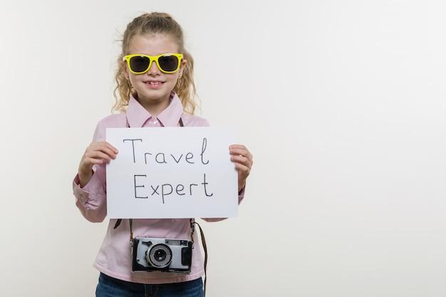 Mädchen, das blatt papier mit einem wort reise-experten hält.