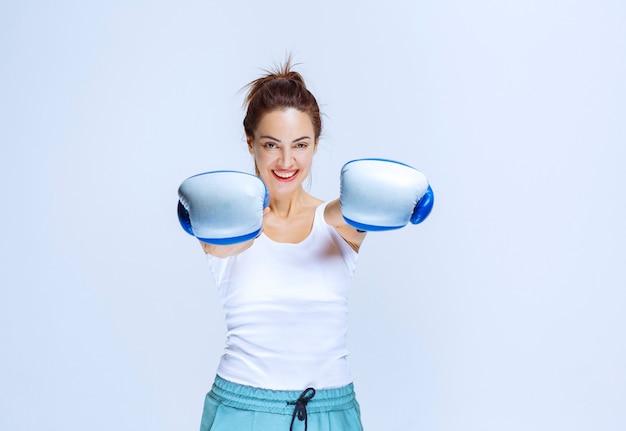 Mädchen, das blaue boxhandschuhe in der hand hält, aber nicht trägt.