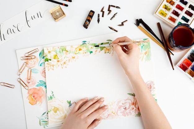 Mädchen, das blumen auf papier mit aquarell malt.