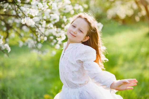 Mädchen, das blumen des apfelobstgartens schnüffelt. garten mit blühenden bäumen