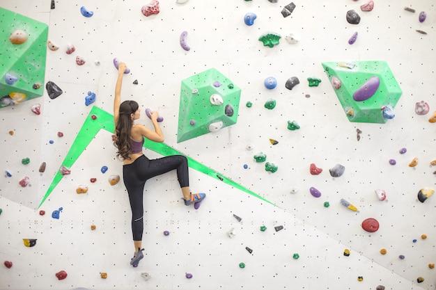 Mädchen, das bouldern in einem kletterzentrum tut