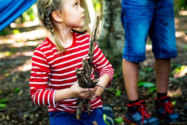 Mädchen, das brennholz im wald sammelt
