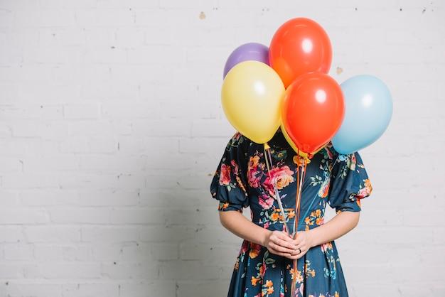 Mädchen, das bunte ballone vor ihrem gesicht steht gegen wand hält
