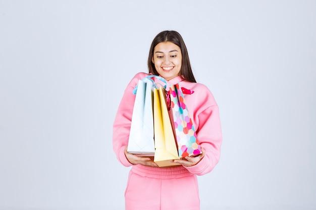 Mädchen, das bunte einkaufstaschen umarmt und sich positiv fühlt.