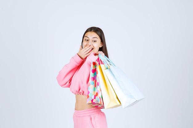 Mädchen, das bunte einkaufstaschen zurück an ihrer schulter hält.