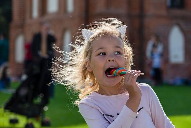Mädchen, das bunte süßigkeiten isst. ein fünfjähriges mädchen in rosa kleidung isst eine bunte süßigkeit am stiel. sonniger sommertag.