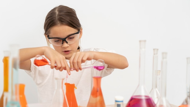 Mädchen, das chemieexperimente mit schutzbrille tut