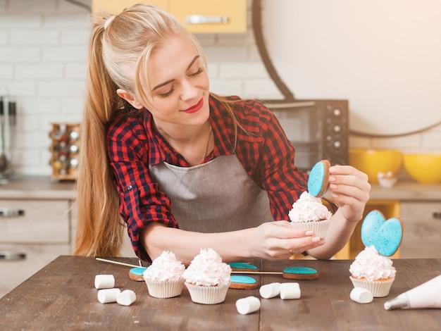 Mädchen, das cupcakes mit weißer creme und blauen cake-pops am küchenholztisch verziert