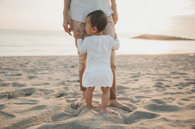 Mädchen, das das bein der mutter beim stehen auf dem strand hält
