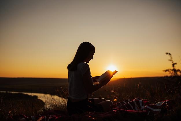 Mädchen, das das buch in einem feld während des schönen sonnenuntergangs liest.