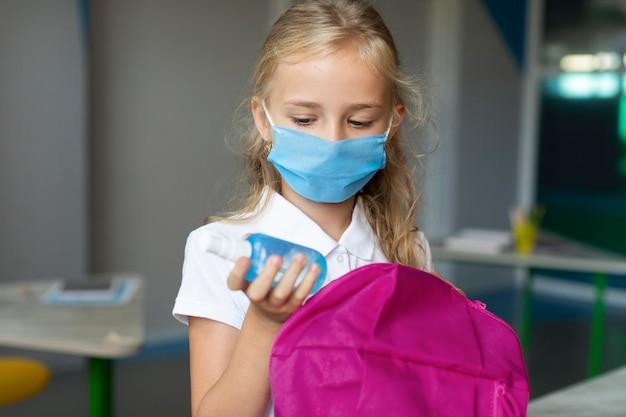 Mädchen, das das desinfektionsmittel aus ihrem rucksack nimmt