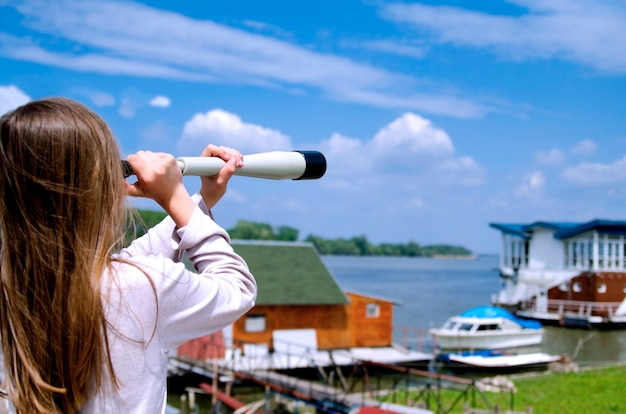 Mädchen, das das flussschwimmhaus und das bootsdorf mit fernglas-teleskop sucht. auf der suche nach dem sommer. kopierraum