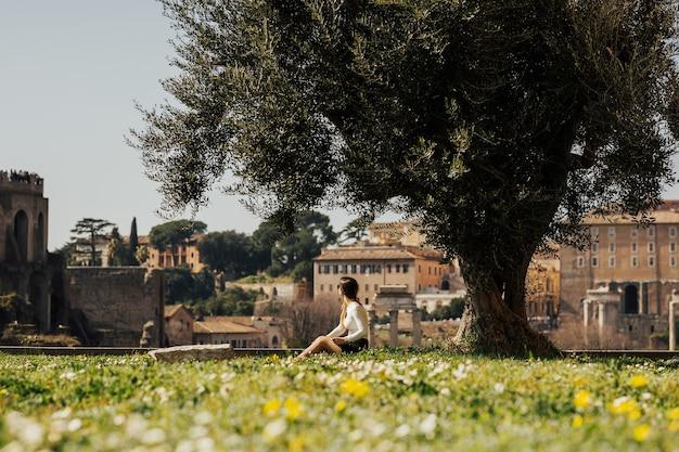 Mädchen, das das forum romanum in rom betrachtet.